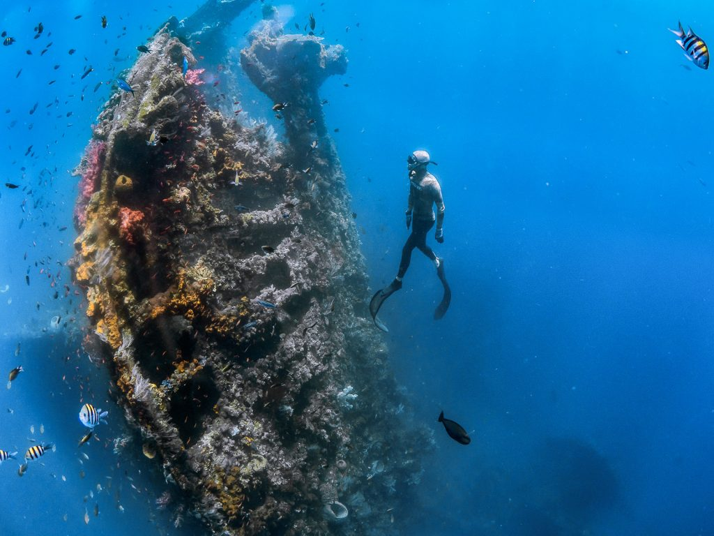 Freediver surfaces on shipwreck in bali.